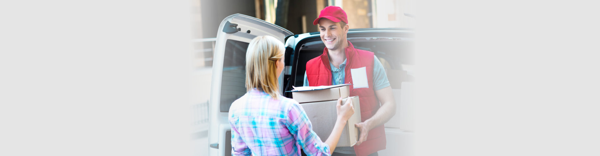 delivery man smiling while giving the package to the customer