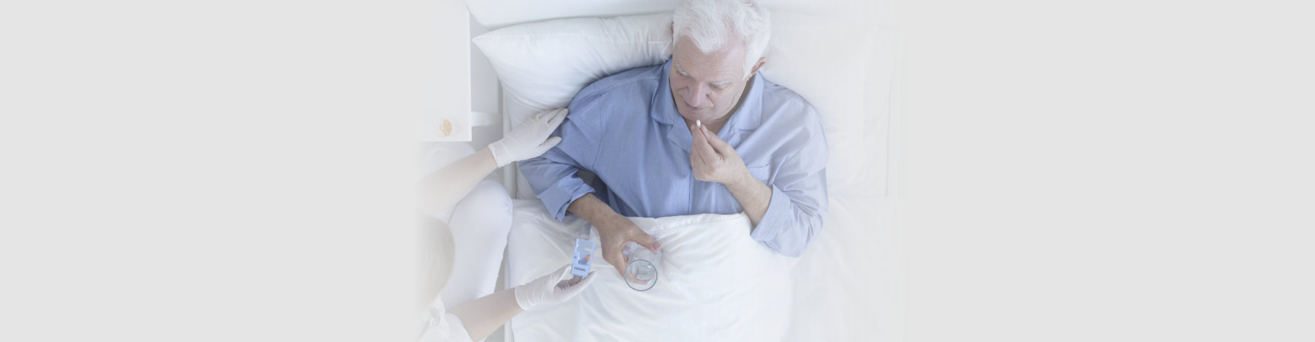senior man lying in bed taking pills with a glass of water